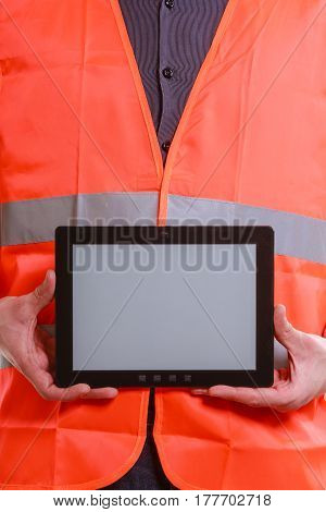 Technological development in company. Part body man worker in orange uniform safety vest with tablet. Repairman inspector at work.