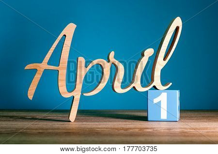 April 1st. Day 1 of month, carved word calendar on wooden table and dark blue background. Spring time.