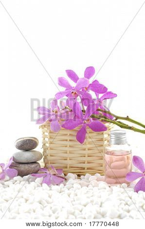 Spa still life with basket of pink orchid with stacked stones and massage oil on zen white pebble