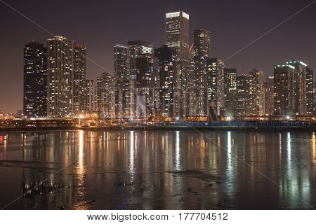 Side view of water flashing light of high-rise houses at night in Chicago city. Panorama concept