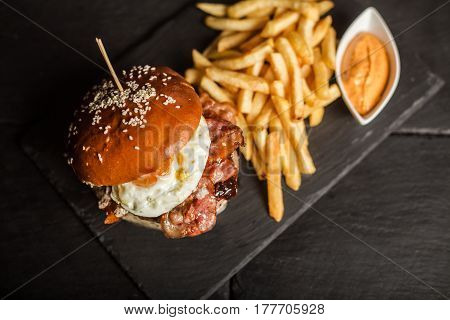 Delicious hamburger with french fries on dark background. Fast food