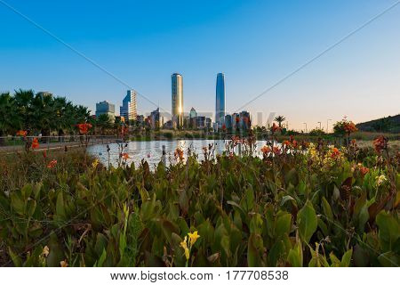Pond at Bicentennial Park in the wealthy Vitacura district and skyline of buildings at financial district Santiago de Chile