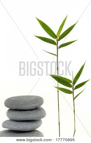 Three zen stones balanced with bamboo leaf