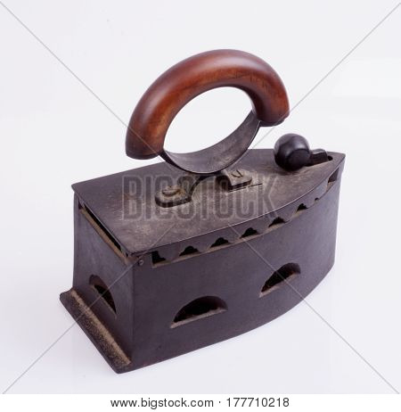 An ancient cast-iron inoculum with a wooden handle on a white background