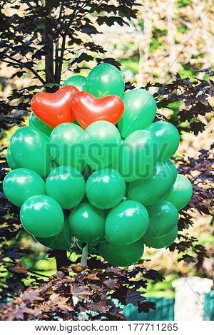 Two red heart shape baloon surraunded with green baloons