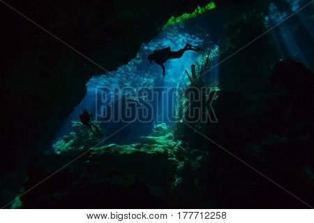 Two divers exploring hidden reefs in the cenote underwater cave of Quintana roo, Mexico
