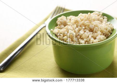 Green ceramic bowl full of brown rice on napkin