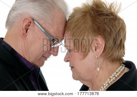 A closeup image of an senior citizen couple standing with forehead to forehead together isolated for white background.