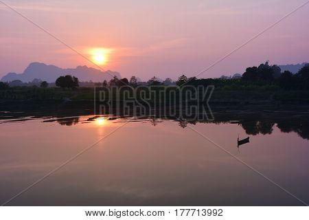 Lonely wooden boat reflecting in the river at the sunset Myanmar.