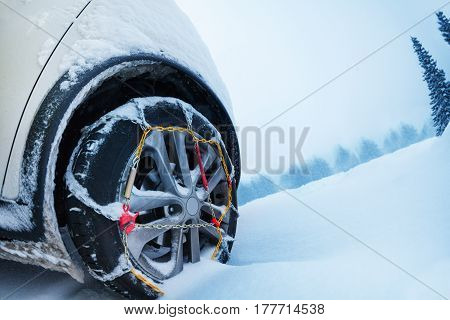 Automobile wheel with ice tire chains on the snow-covered mountain road