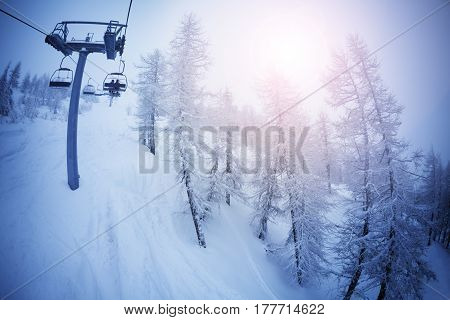 View from the cabin of chairlift on snowcapped slopes and trees at sunny day