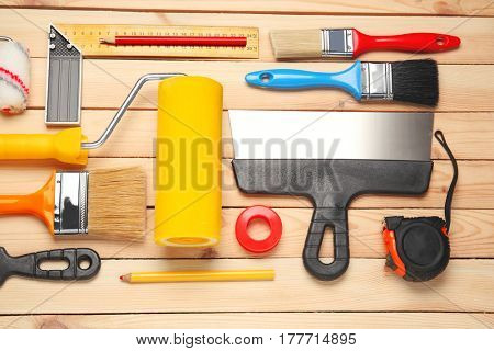 Flat lay composition of decorator and house renovation tools on wooden background