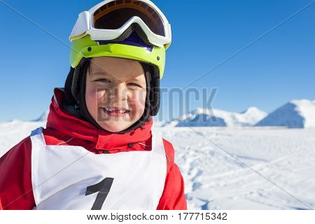 Portrait of happy little skier in safety helmet and ski mask at sunny snowy day
