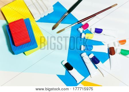 Top view picture of brushes, tubes of multicolored paints, modeling clay and color paper