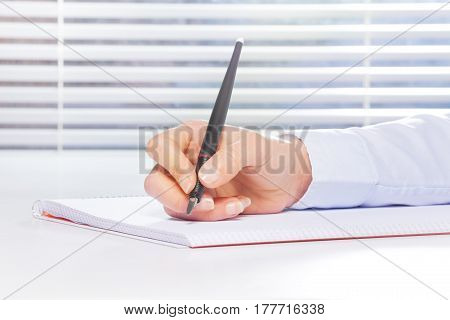 Woman's hand making notes on the ring-bound notebook with fountain pen at the table