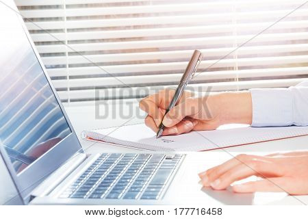 Student's hands writing on ring-bound notebook with fountain pen next to the laptop at the table
