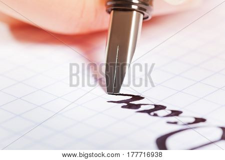 Close-up picture of fountain pen writing the word Dear on graph pad
