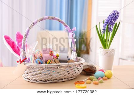 Beautiful Easter basket with traditional decorations and treats on light wooden table