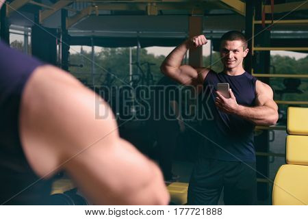 Young handsome man taking selfie in gym
