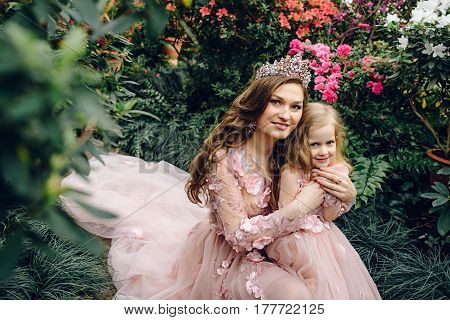 yuong Mom and daughter in luxurious peach-colored dresses in a flowery garden