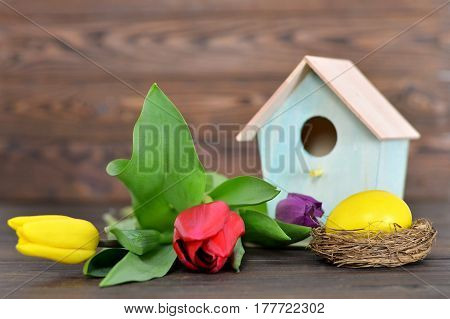 Happy Easter: Easter egg in the nest birdhouse and spring flowers