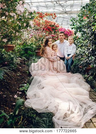 Young happy family - mom dad daughter and son in a blooming spring garden