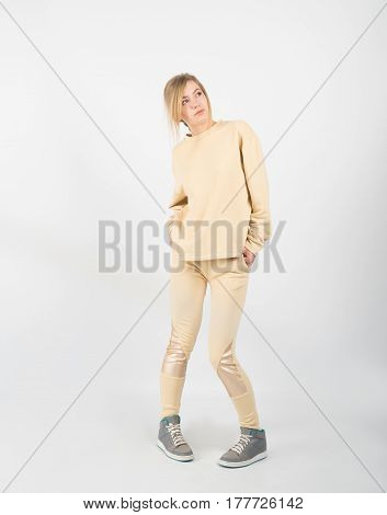 Young beautiful girl wearing yellow clothes and sneakers posing isolated on white background