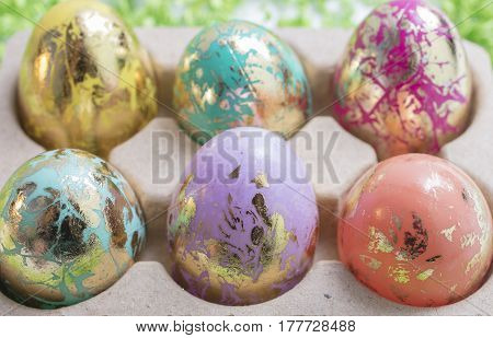 Foiled and Colorful Easter Eggs in Pink Aqua Yellow Orange and Gold in an egg container