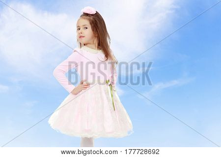 Dressy little girl long blonde hair, beautiful pink dress and a rose in her hair.She keeps hands on hips.On the background of summer blue sky and fluffy clouds.