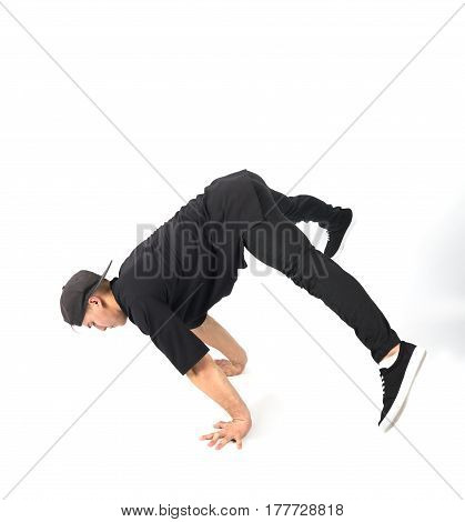 Young muscular man stands on his hands. He is wearing black clothes and snapback on white background