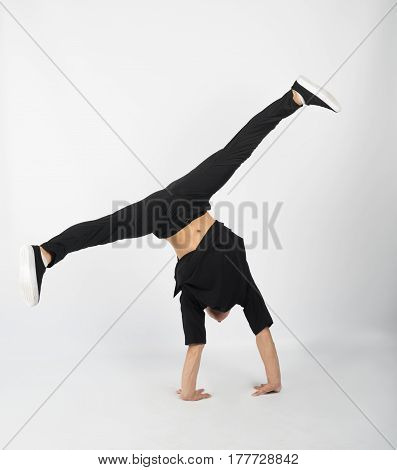 Young muscular breakdancer man stands on his hands. He is wearing black clothes on white background