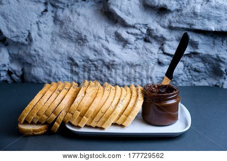Sweet chocolate cream in jar on table. Nutella with buttered bread