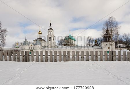 A view of the Tolga convent from the side of the Volga River. In the foreground there is snow and a wooden fence.