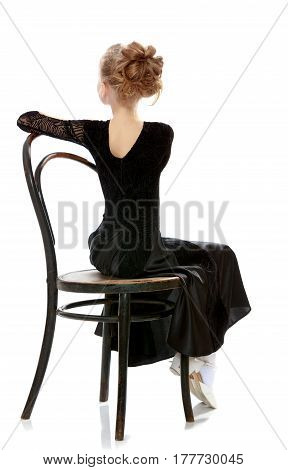 The slender little blonde girl dancer in the long dress of black color made specifically for performing .Girl sitting on an old Viennese chair turned away from the camera.