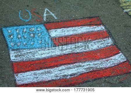 American flag drawn in chalk by children on a driveway.