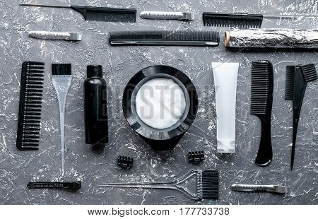 hair dye in bottle with brush in hairdress concept on gray table background top view