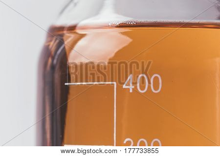 Glassware with scale with colored liquids, laboratory equipment concept, macro photo, abstract background