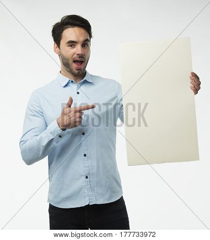 Young happy man portrait of a confident businessman showing presentation, pointing on paper placard over gray background. Ideal for banners, registration forms, presentation, landings, presenting concept.