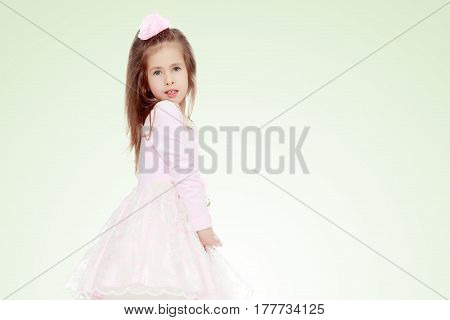 Dressy little girl long blonde hair, beautiful pink dress and a rose in her hair.She turned sideways to the camera and folded his hands in front of him.