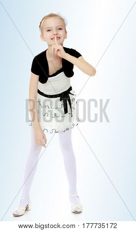 Beautiful little blonde girl dressed in a white short dress with black sleeves and a black belt.Girl keeps the index finger around the lips . The gesture of silence.On the pale blue background.