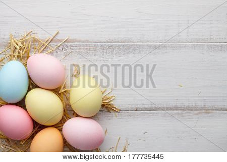 Colorful Easter eggs on white wooden background