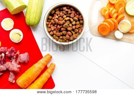 Fresh sliced vegetables and dry petfood on white kitchen table background top view mock up