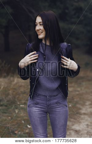 Girl with dark hair in the forest. She wears a black leather jacket and gray jeans. A woman of model appearance stylishly dressed.