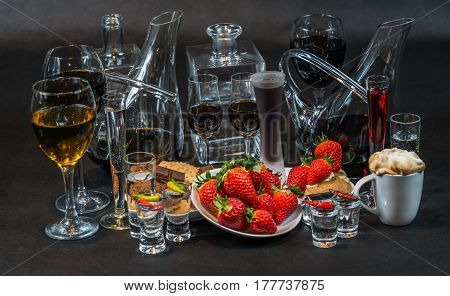 Liquors, Vodkas And Wines In Various Glasses And Decanters, Strawberries And Shortbread Cookies