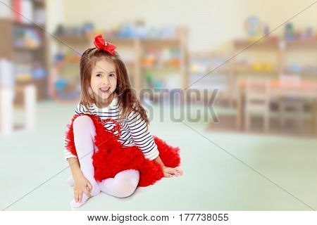 Little girl in a red skirt and bow on her head.She hugged the hand to the knee.In the Montessori room the children's garden where there are shelves with toys and material.