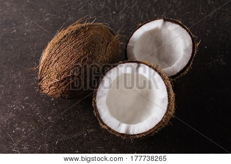 A broken coconut on a dark marble background. Exotic large coconut walnut. Coconut concept. Brown big coconut on the table
