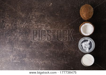 Spa treatments and massages. Spa concept. Coconut cream for spa coconut milk and butter on a dark marble background. Exotic large walnut. Personal care. Spa treatments