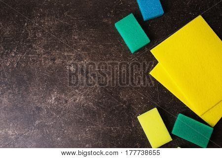 Yellow napkins colored and metal sponge on a dark marble background. Items for hygiene and washing dishes. Sponge flat lay. Flat lay sponge