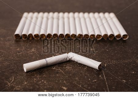 Cigarette on a dark marble background. Bad habit. Care for health. Leave off smoking. Cigarette concept. Broken cigarette on the table. Cigarette flat lay