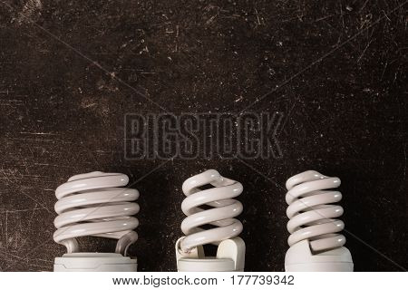 Fluorescent light lamp bulb on a dark marble background. To save energy. Eco concept fluorescent light bulb. Fluorescent lamp